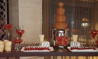 Strawberries dipped in warm chocolate flowing in the fountain.  Dreams are made of this.